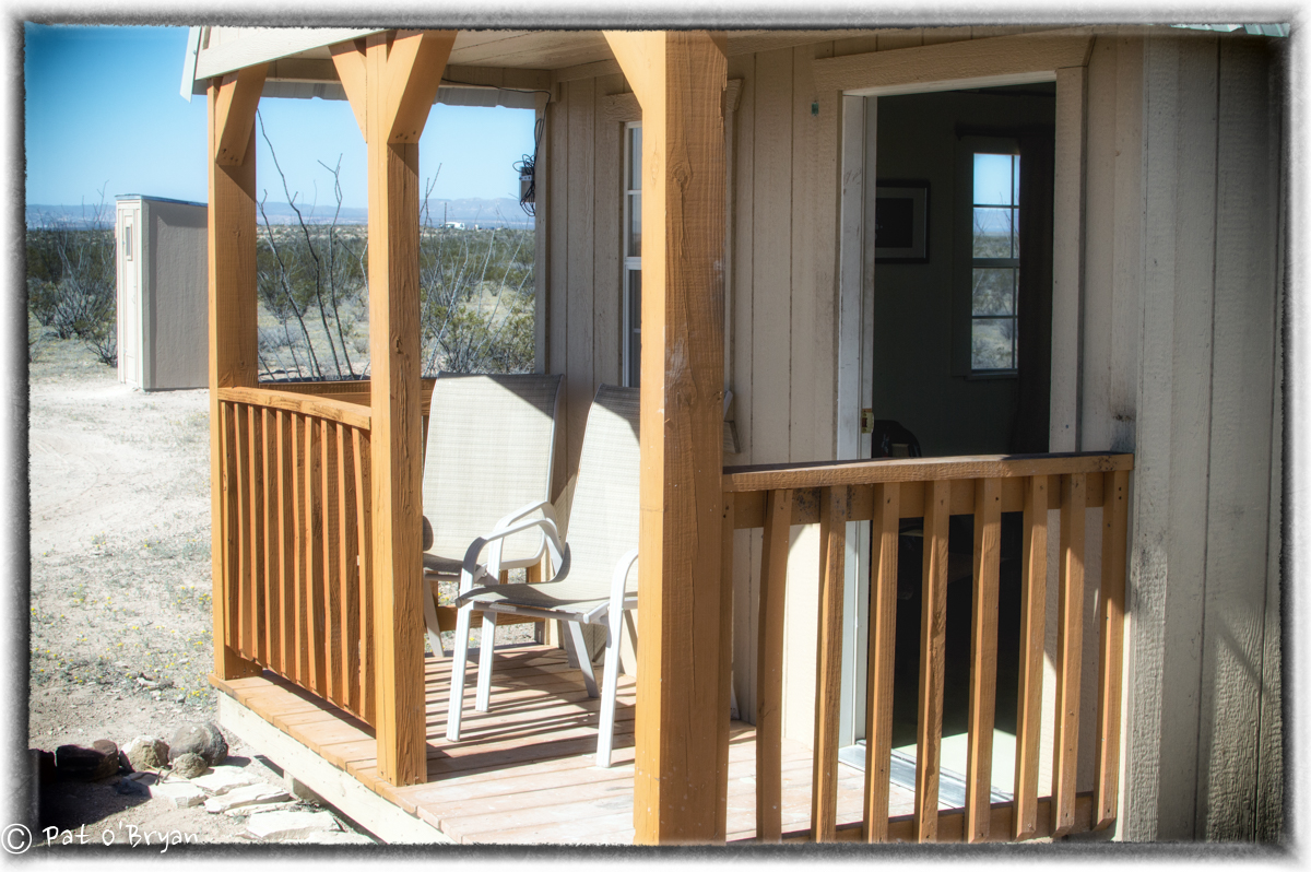 Porch with two comfy chairs- outdoor bathroom.